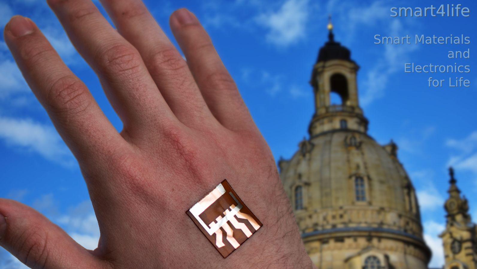 Das Zukunftscluster smart4life – Smart Materials and Electronics for Life verbindet elektronische und biologische Systeme. Im Vordergrund ist eine menschliche Hand mit einem flexiblen elektronischen Dünnschichtbauteil zu sehen, im Hintergrund die Frauenkirche als Symbol für die Region Dresden.